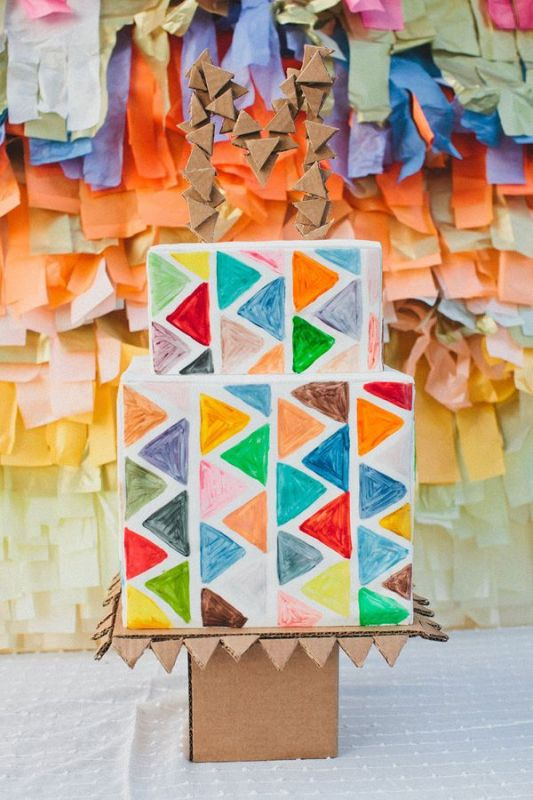 a bright square wedding cake with colorful triangles is a bold and cool idea for a mid century modern wedding