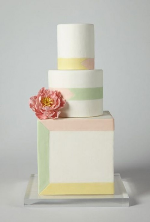 a pretty wedding cake with round and a square tier, with colorful lines and a design that highlights the square shape of the cake