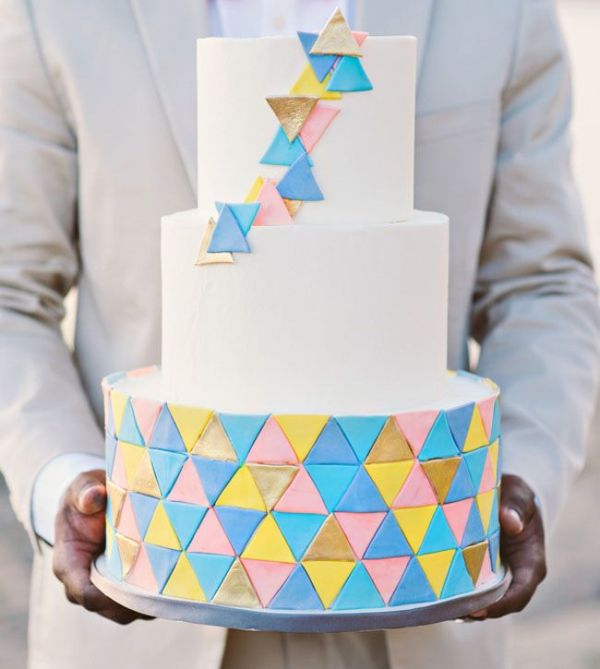 a round wedding cake decorated with colorful triangles and 3D triangles on the upper tiers is a lovely idea for a modern and colorful wedding
