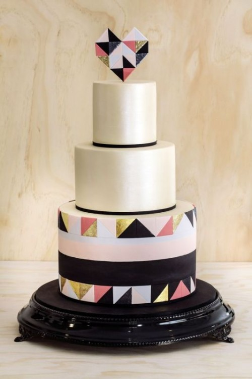 a round wedding cake with black lines, with a bold pink, gold and black triangle tier and a matching geometric heart topper is pure fun and chic