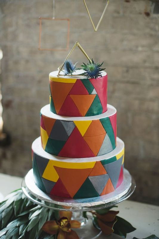 a colorful round wedding cake with bright triangles all over the cake, with a himmeli topper and thistles on top is a bright and fun idea for a wedding