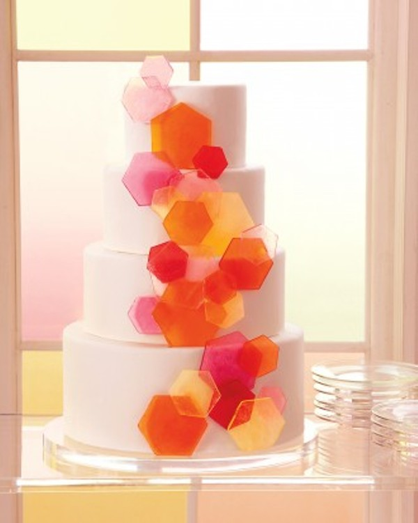a white round wedding cake decorated with colorful hexagons is a lovely idea for a 70s or a mid century modern wedding