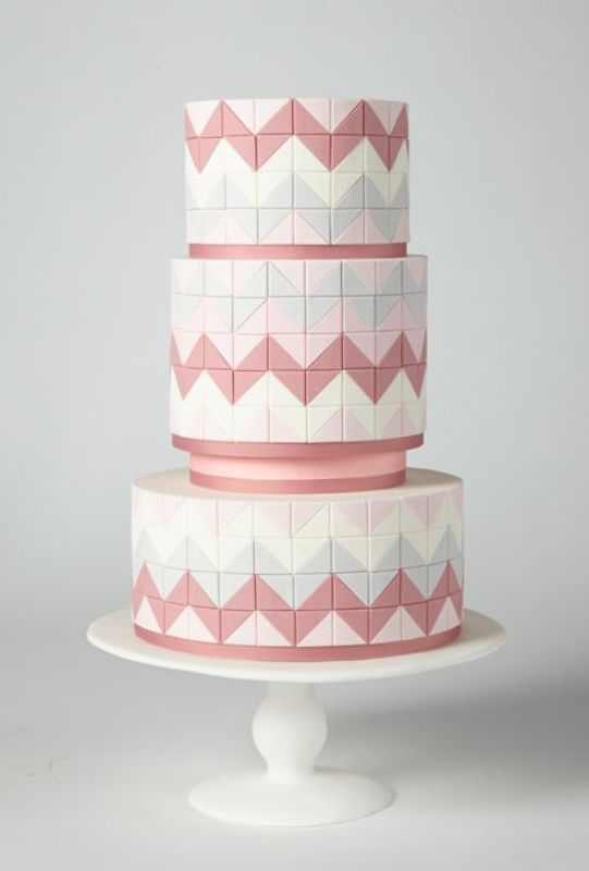 a white, pink and grey wedding cake with squares covering its surface and chevron patterns for more eye catchiness