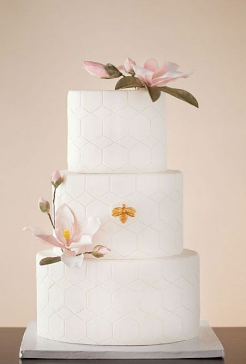 a white round wedding cake covered with hexagon patterns and with a couple of large sugar blooms looks refined and modern