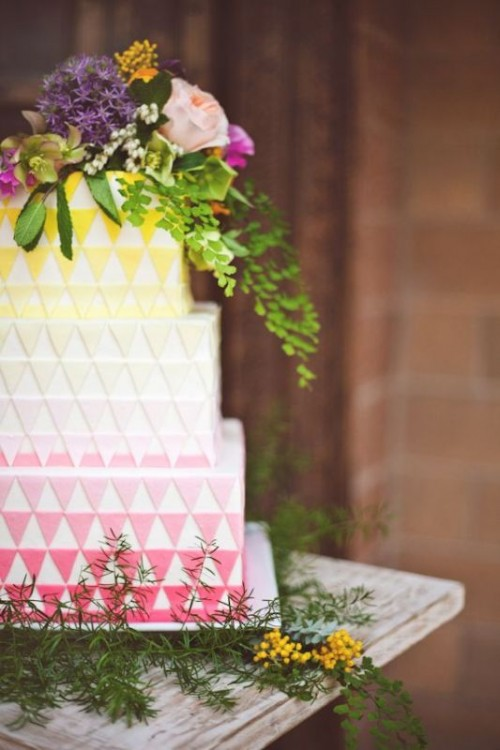 a colorful modern wedding cake with an ombre effect, with yellow, white and pink triangle tiers and super bold blooms and greenery on top the cake