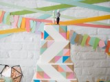 a colorful square wedding cake with super bright triangles covering it and fun cake toppers for a bright mid-century modern wedding