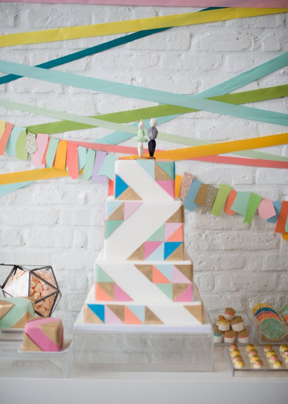 a colorful square wedding cake with super bright triangles covering it and fun cake toppers for a bright mid century modern wedding