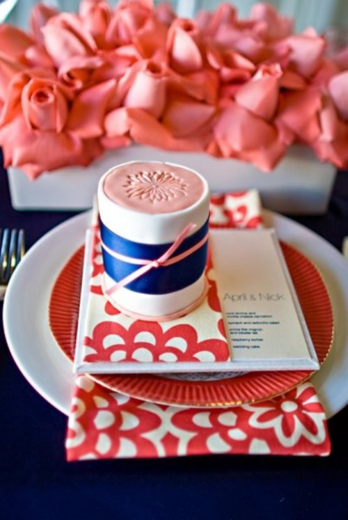 coral blooms, a coral plate and menu and a coral and navy gift box with a bow for each place setting