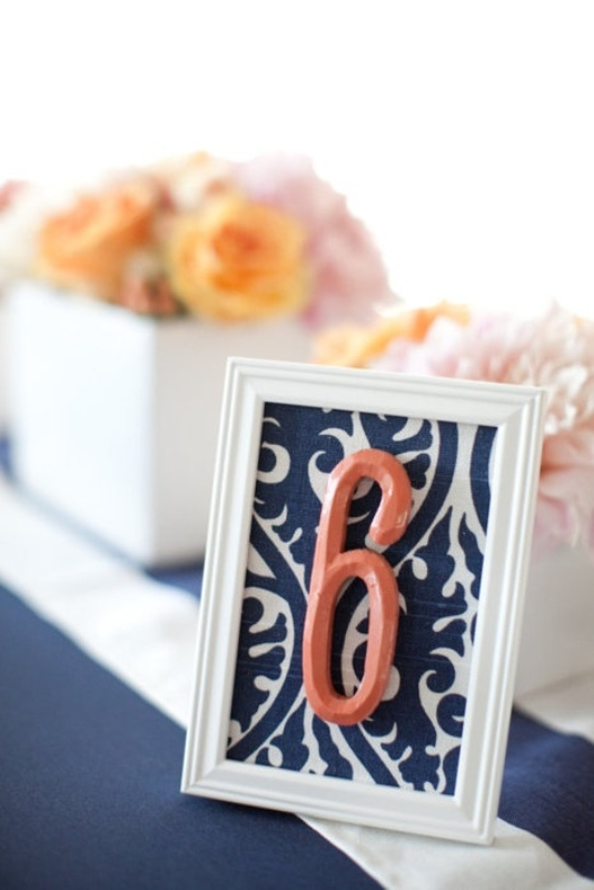 a printed navy and white table number and a coral number itself to highlight the color scheme you've chosen