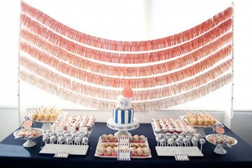 a navy dessert table with lots of sweets and a navy and coral wedding cake plus ombre coral wedding garlands over the table