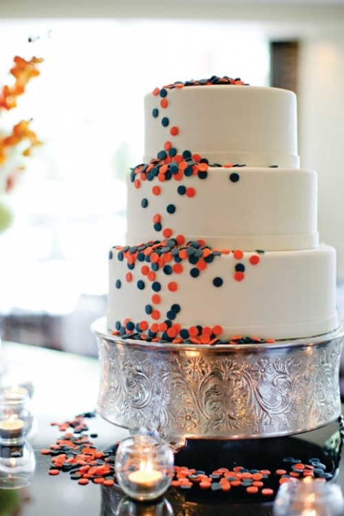 a white wedding cake with navy and coral piink polka dots for decor is an unobtrusive way to rock the color scheme