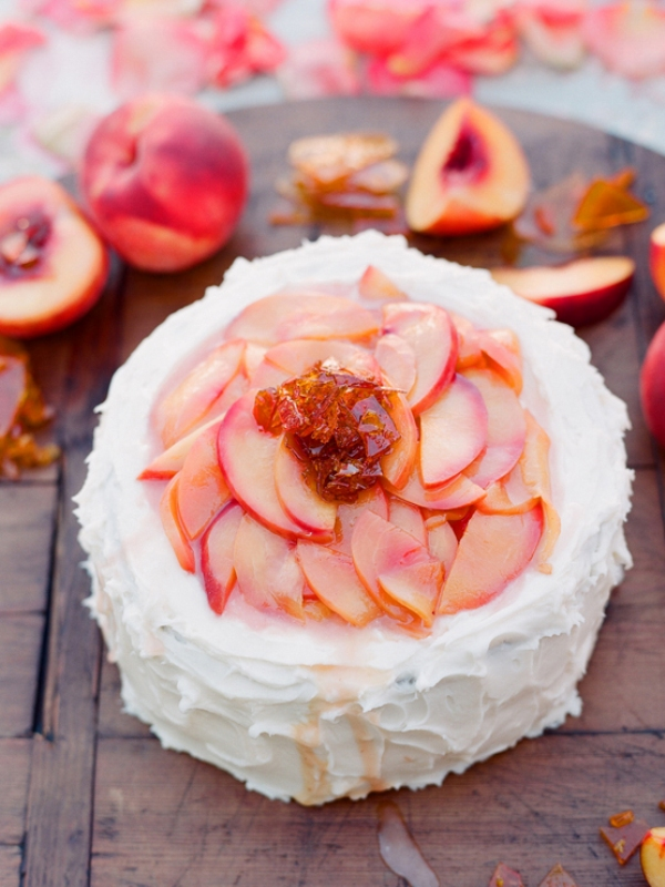 a white textural wedding cake topped with fresh peaches   a coral touch, which is also delicious