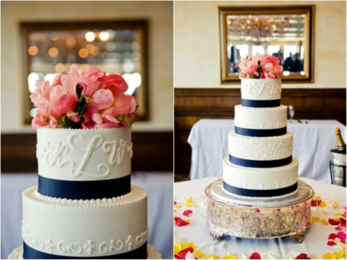 a white textural wedding cake with navy ribbons and coral pink blooms on top is a chic idea