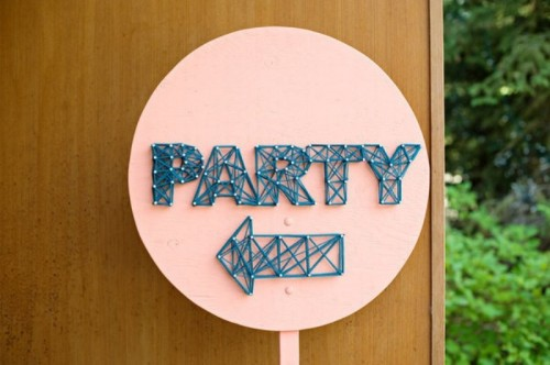 a fun circle coral sign with navy string art showing where to go is a very creative and trendy idea