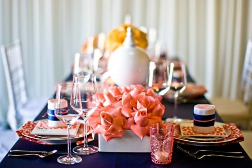 a bold navy and coral table setting with coral blooms and candle holders, a navy tablecloth and prints