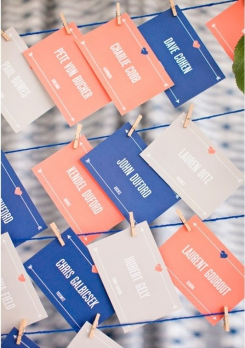 grey, coral and blue escort cards with white letters are a very fun idea of a wedding seating chart