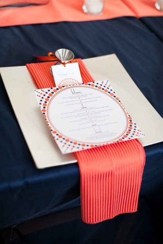 a navy tabecloth, a large charger, a striped coral napkin and a printed menu for a bold place setting