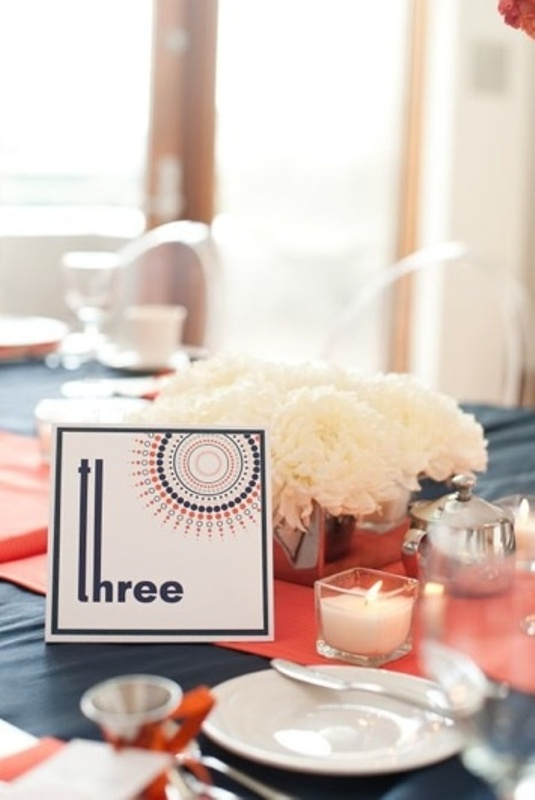 a navy tablecloth, a coral table runner, neutrals blooms and candles and a bold printed table number