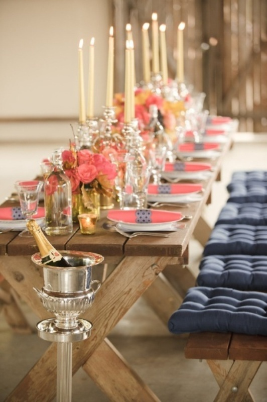 a rustic tretle table with coral blooms and a coral napkin with a navy napkin ring and a wodoen bench with tufted navy cushions