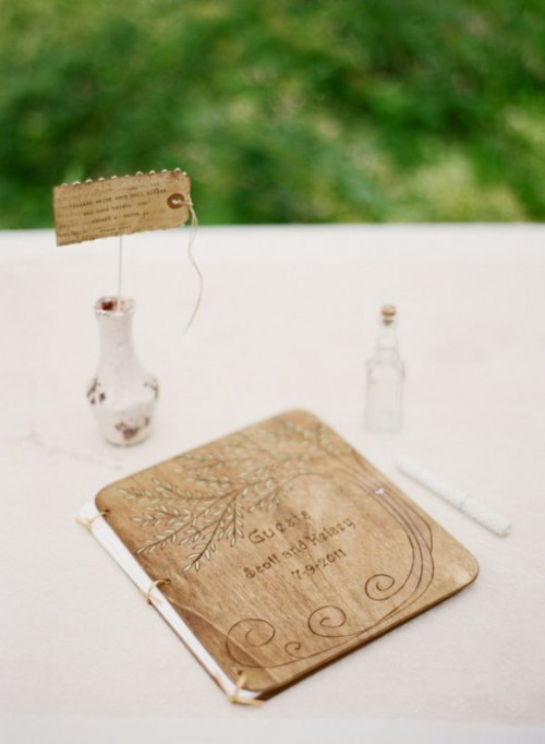 a creative guest book with a wooden cover, which is wood burnt, and usual pages inside