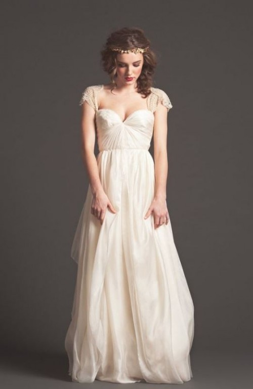 a beautiful a-line wedding dress with a sweetheart neckline, short embellished sleeves and a full skirt