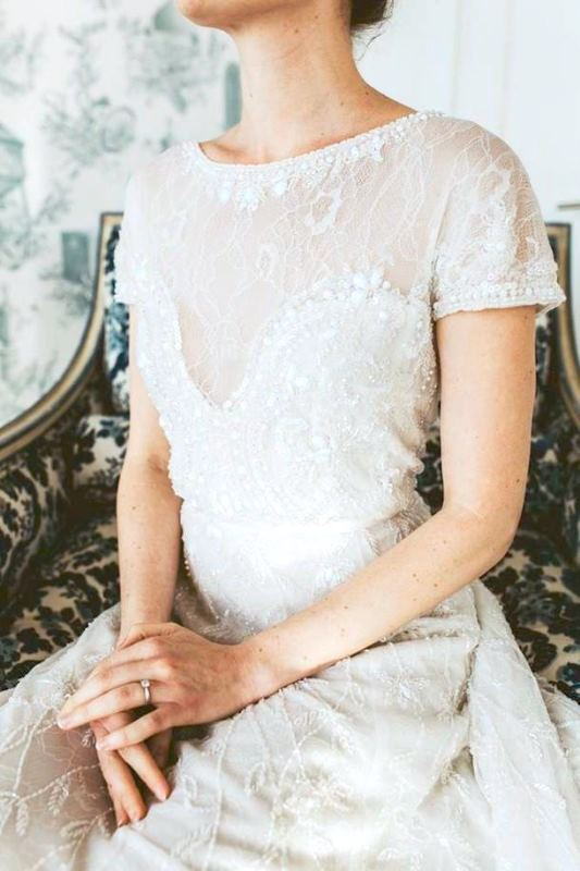a lace A line wedding dress with an embellished corset, neckline and short sleeves looks royal like
