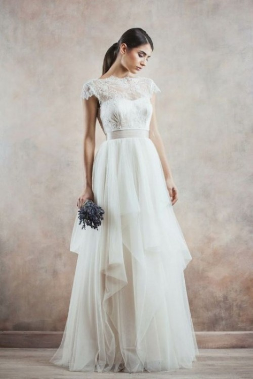 an A-line wedding dress with an illusion neckline, sheer sleeves and a layered skirt looks very eye-catchy