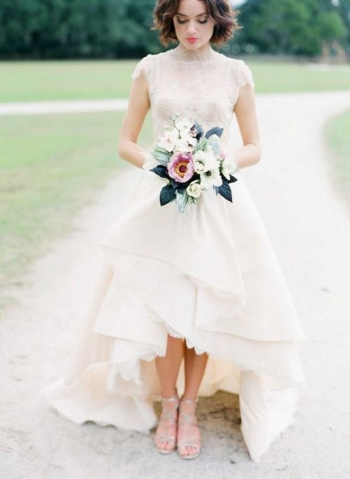 a statement A-line wedding dress with a turtleneck, short sleeves and a layered high low skirt with a train