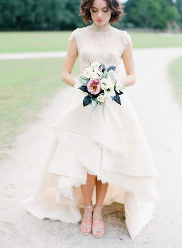 a statement A line wedding dress with a turtleneck, short sleeves and a layered high low skirt with a train