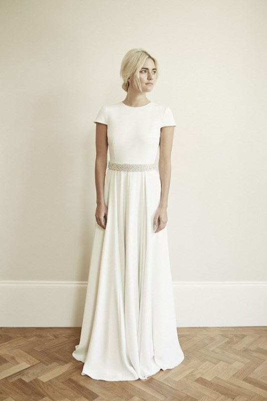a modern plain wedding dress with a pleated skirt, a high neckline, short sleeves and an embellished sash