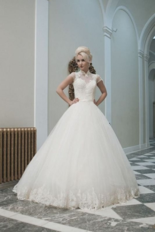 a wedding ballgown with a lace bodice with short sleeves, an illusion neckline and a full skirt with a lace trim