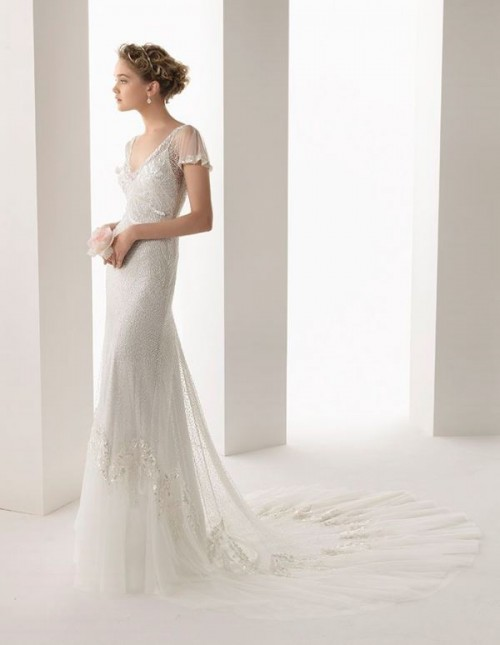 a fitting lace wedding dress with a V-neckline, sheer sleeves, an embellished bodice and a short train