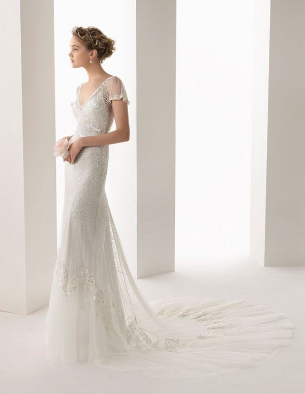 a fitting lace wedding dress with a V neckline, sheer sleeves, an embellished bodice and a short train