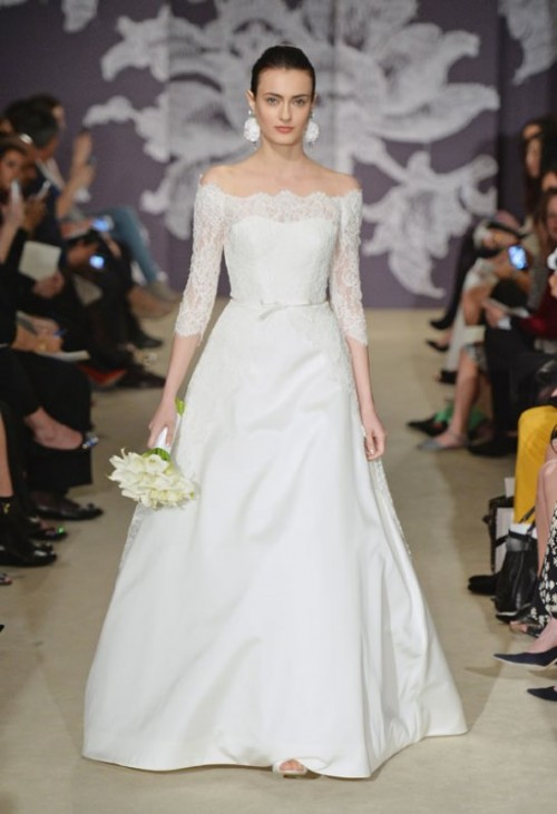 an off the shoulder a-line wedding dress with a lace bodice and short sleeves plus a plain full skirt with a train