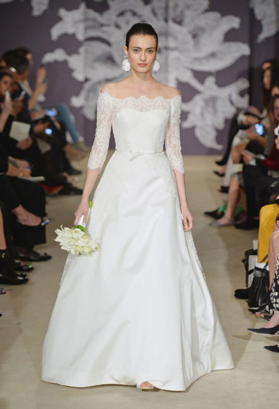 an off the shoulder a line wedding dress with a lace bodice and short sleeves plus a plain full skirt with a train