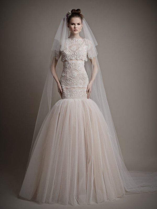 a whimsical lace mermaid wedding dress with a full tulle skirt, a high neckline, short sleeves and a veil