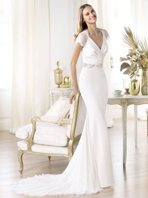 a fitting plain wedding dress with a V neckline, short lace sleeves, an embellished sash and a train