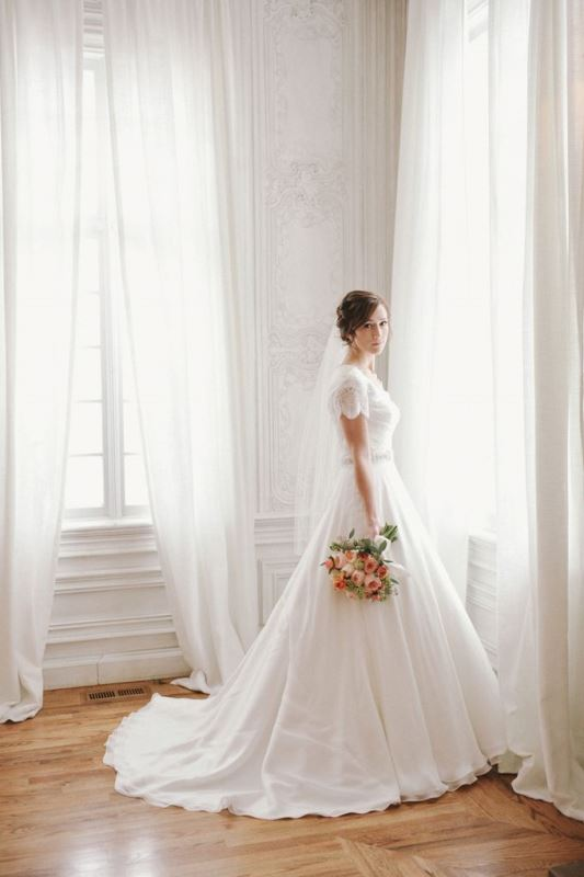 a romantic A line wedding dress with short draped sleeves, a deep neckline, an embellished sash and a train