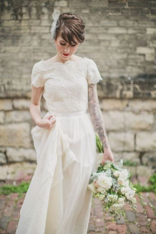 a lace A-line wedding dress with a lace bodice, short sleeves, a high neckline and a pleated maxi skirt