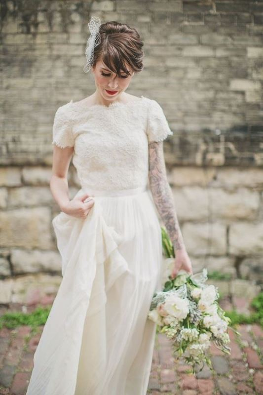 a lace A line wedding dress with a lace bodice, short sleeves, a high neckline and a pleated maxi skirt