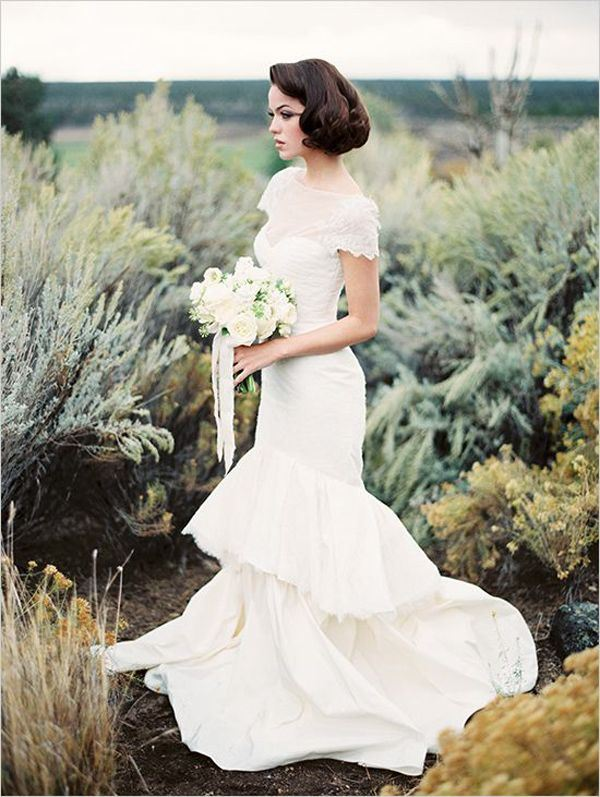 a whimsy mermaid lace wedding dress with a high illusion neckline, short sleeves, a ruffle layered skirt and a short train
