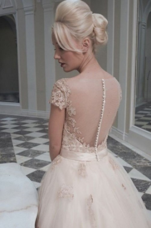 a nude lace wedding ballgown with a lace bodice, an illusion back on buttons and a full skirt with appliques