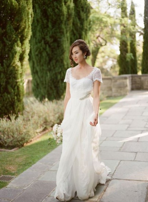 a chic lace A-line wedding dress with a simple neckline, short sheer sleeves and a train