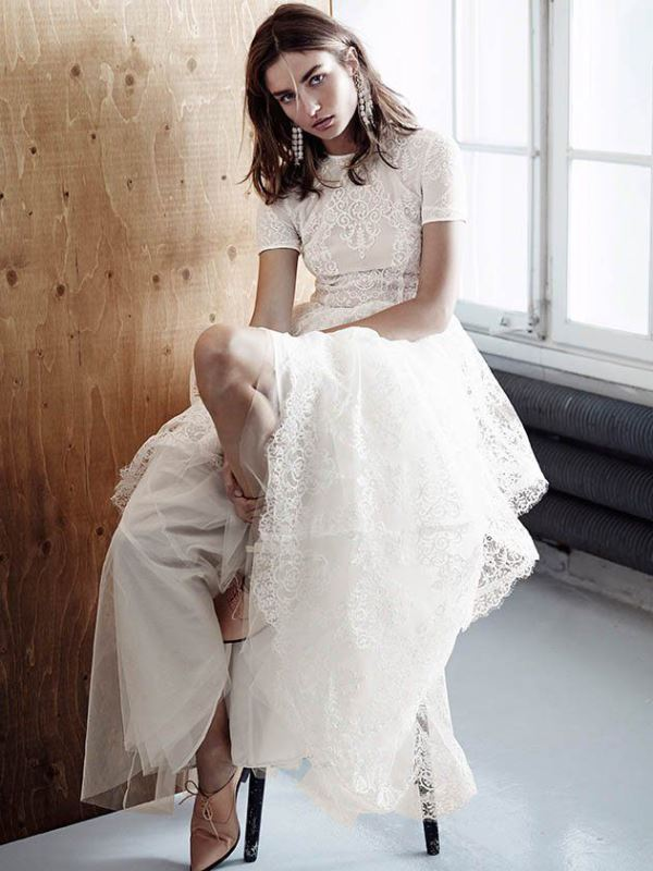 a modern lace A line wdding dress with a high neckline, short sleeves, blush shoes and statement earrings