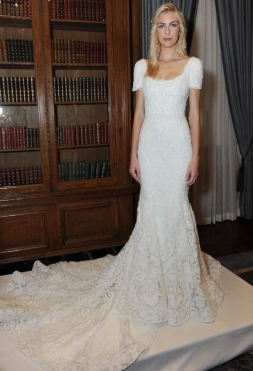 a fitting lace embellished wedding dress with short sleeves, a scoop neckline and a train