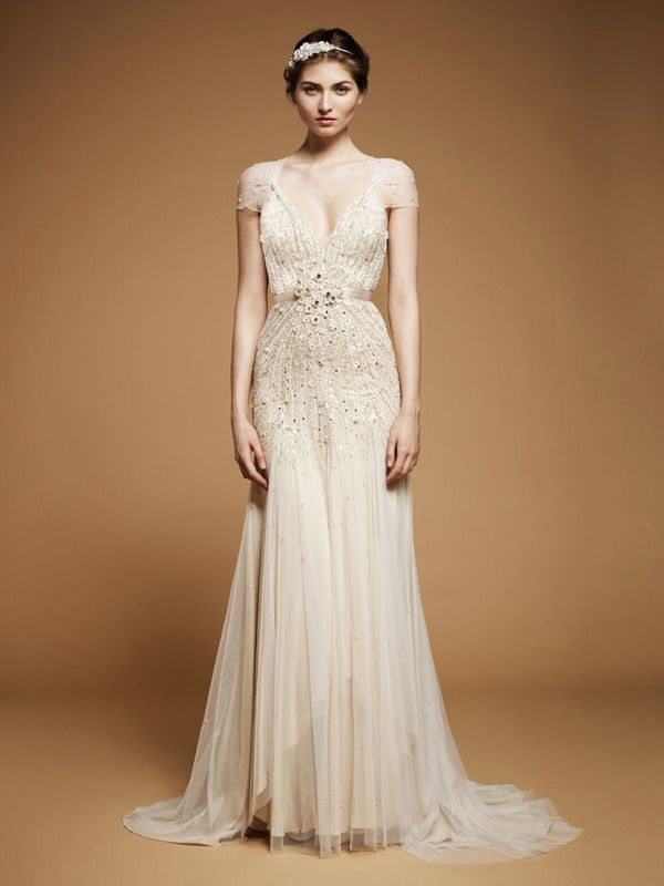 an embellished A line art decor wedding dress with a deep neckline, cap sleeves and a small train