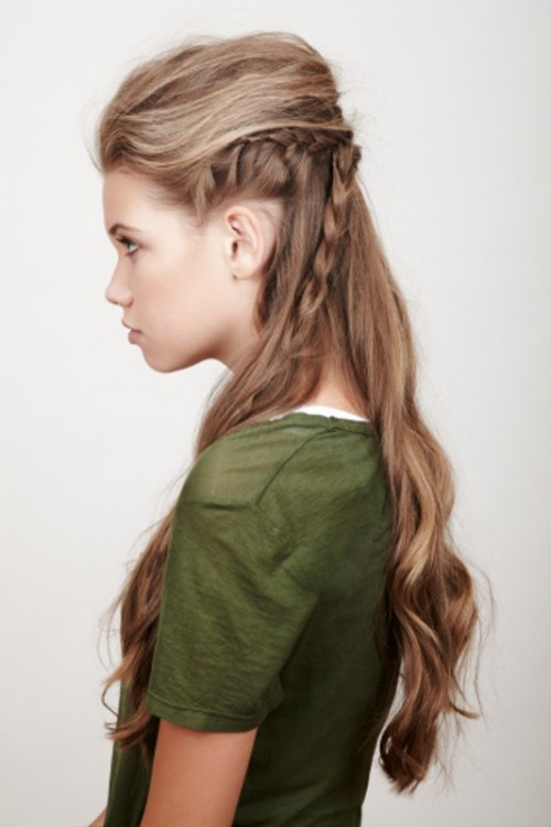 a folksy half updo with a messy volume on top, a braided halo and braids down plus waves down feels Viking-like