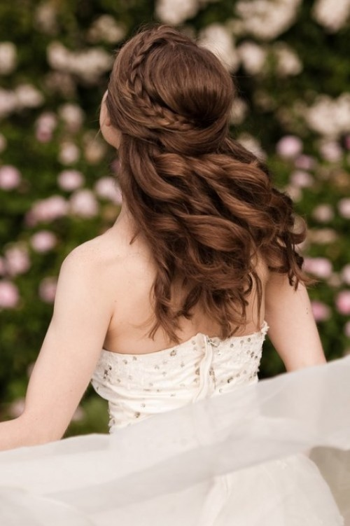 a romantic wedding half updo with a braid on one side and a twist on the second side, with waves down