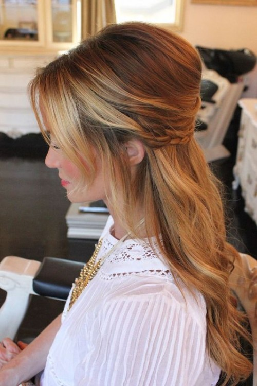 a chic yet relaxed wedding half updo with a volume on top, side bangs, a braided halo and waves down is very romantic