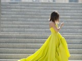 a strapless lemon-colored wedding ballgown with a high low skirt and a train is bold and very modern